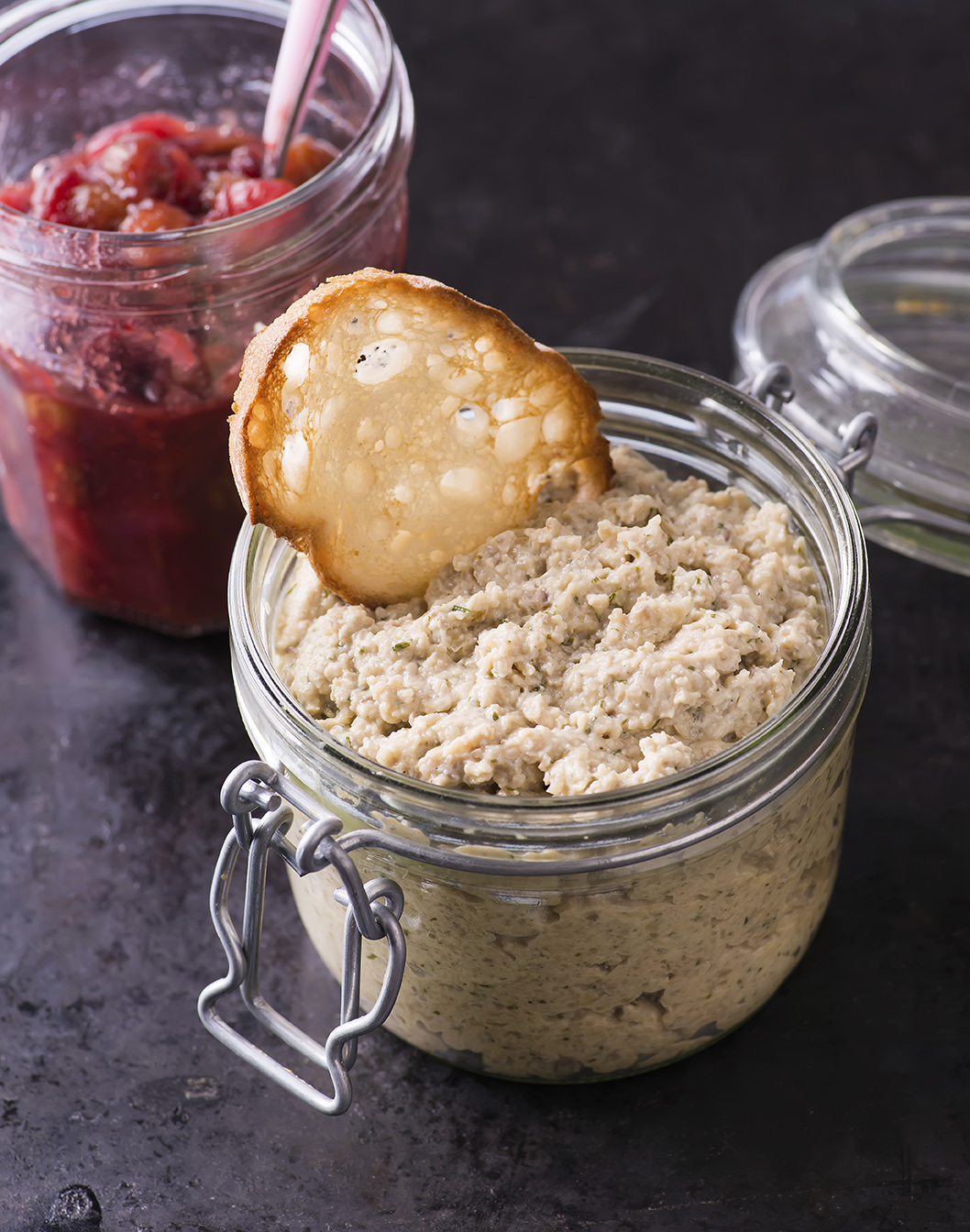 Mushroom pate and cranberry relish in a jars over dark background, selective focus
