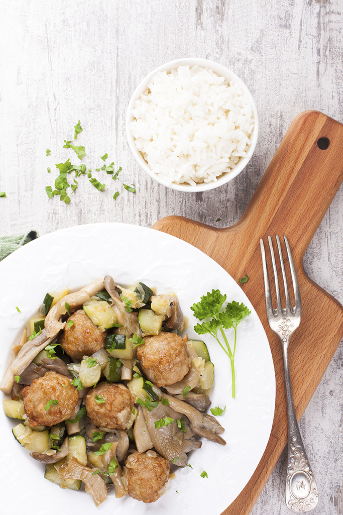 Chicken meatballs with oyster mushrooms, zucchini and rice on white plate and wooden cutting board.  Healthy food concept.  Top view.